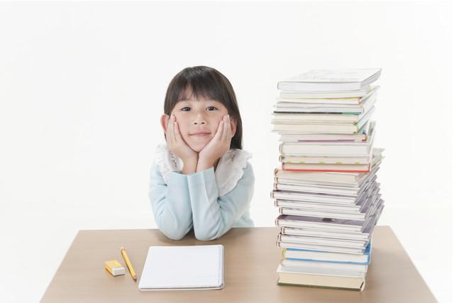 積み上げられた教科書の横でこちらを見ている女の子