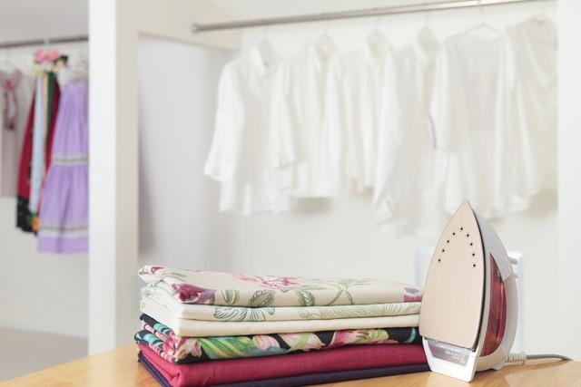 白いシャツや衣類がかけられている、テーブルの上にアイロン