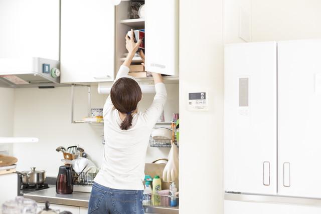 キッチンの収納を整理している女性