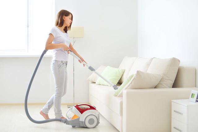 ソファに掃除機をかける女性