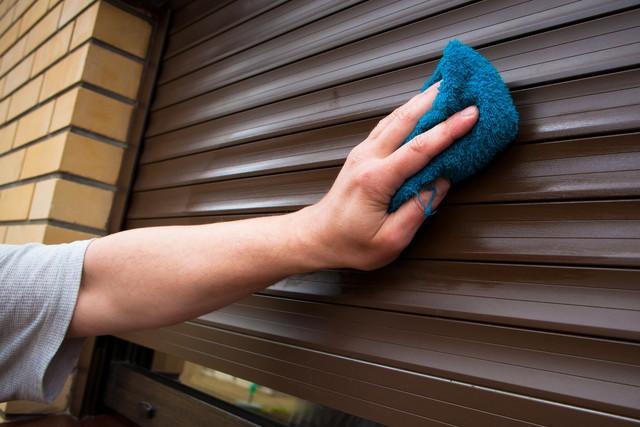 雨戸を掃除している人の手