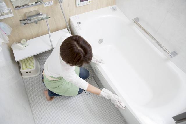 お風呂のピンク汚れを掃除する女性