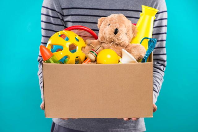 おもちゃが入った箱を持つ人、水色の背景