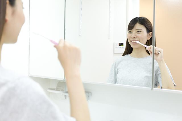 洗面台で歯を磨く女性