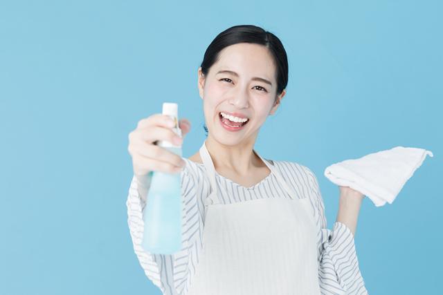 スプレー洗剤と雑巾を持っているエプロン女性