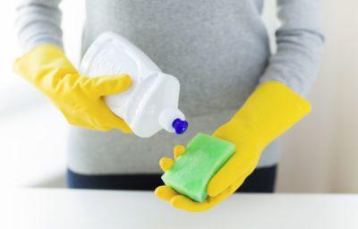 黄色いゴム手袋とスポンジを持つ手