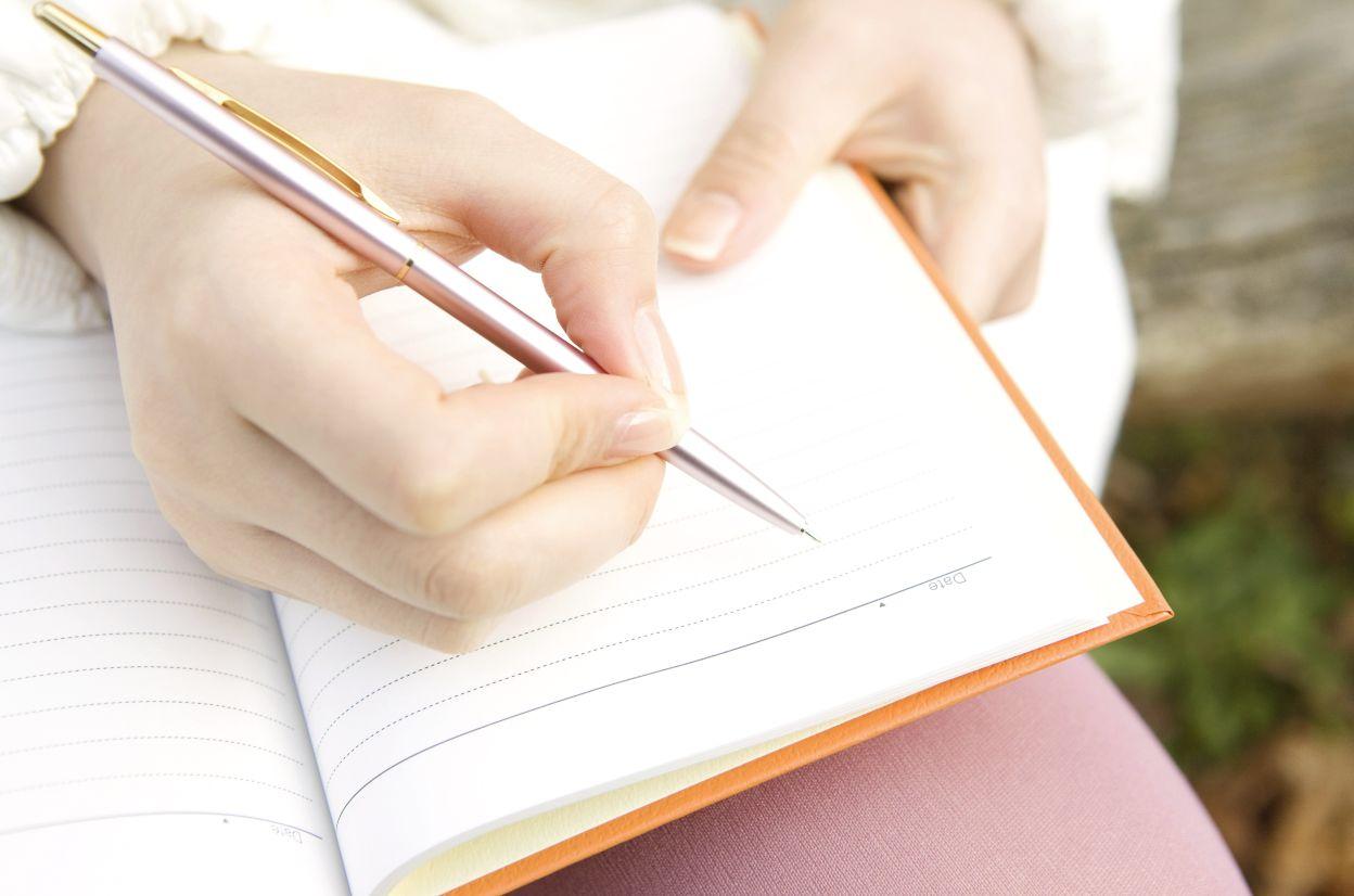 ノートとボールペンを持つ手