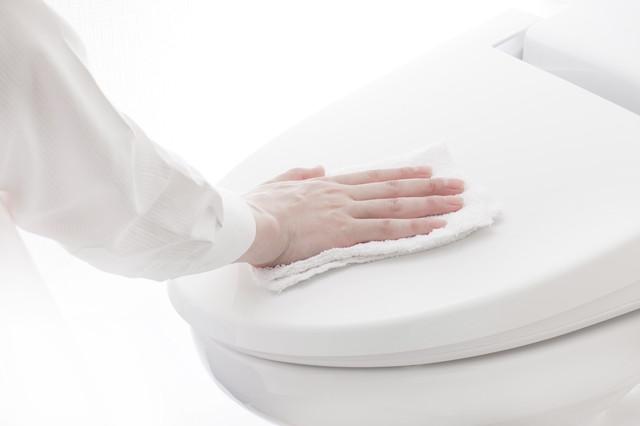 便座のフタを拭く手