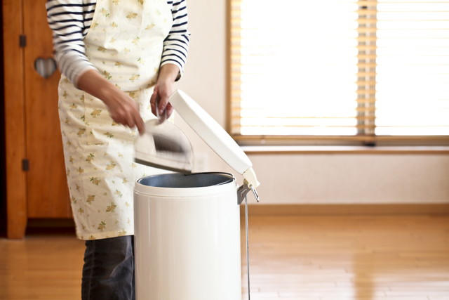 ゴミ箱とエプロンをした女性