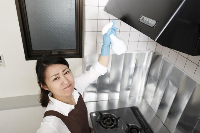 台所の換気扇を掃除している主婦