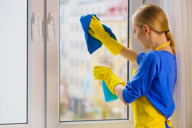 窓を掃除している女性