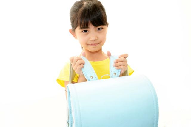 水色のランドセルを持つ小学生