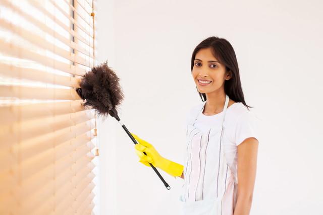 ブラインドを掃除している女性