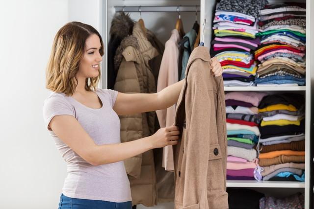 コートを手に持つ女性
