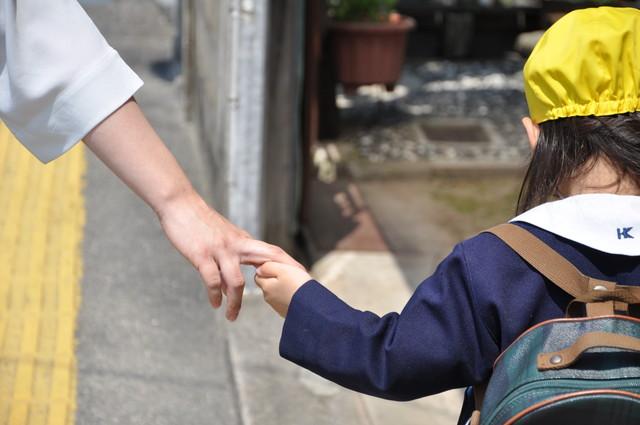 手を繋いでいる制服を着た子供