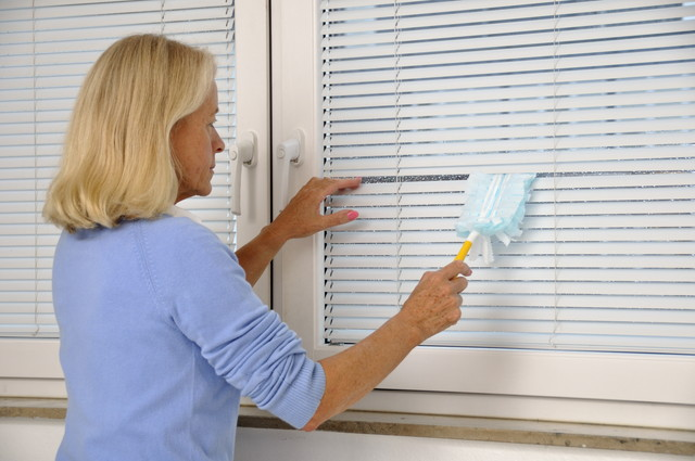 白いブラインドを掃除している女性