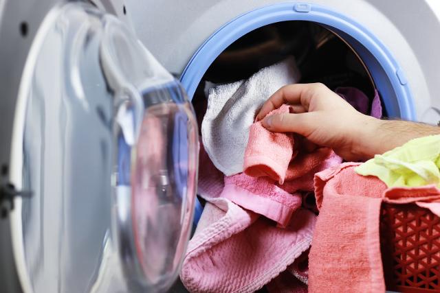 乾燥機からタオルを出す手