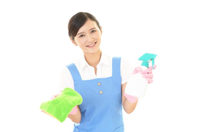 スプレーと雑巾を持って掃除をする女性
