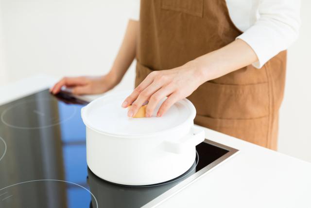 ihクッキングヒーターに鍋を置く女性