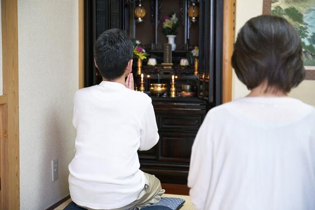 仏壇をおがむ夫婦