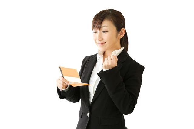 通帳を見て喜ぶ女性