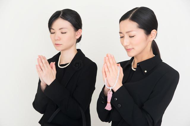 喪服を着て手を合わせる女性が2名