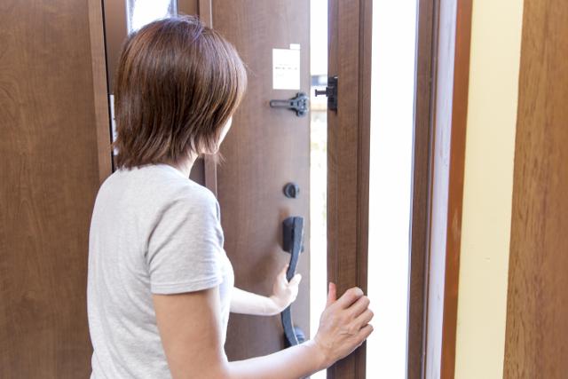 玄関を開ける女性