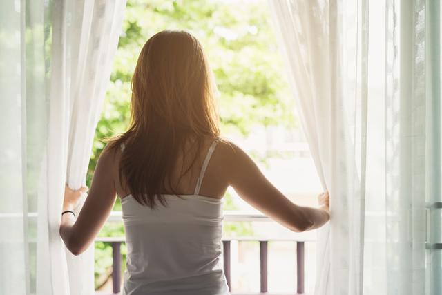窓を開ける女性の後ろ姿