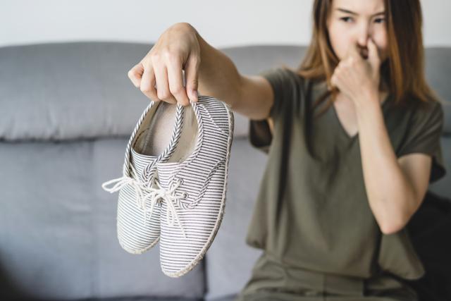 靴の臭いを嫌がる女性,鼻をつまむ女性