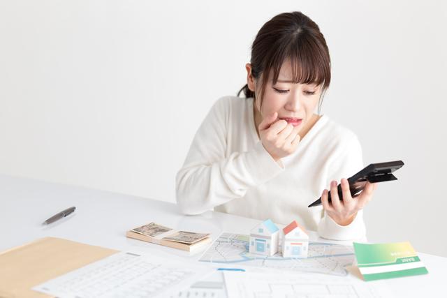 お金計算で電卓を見て悲しんでる女性