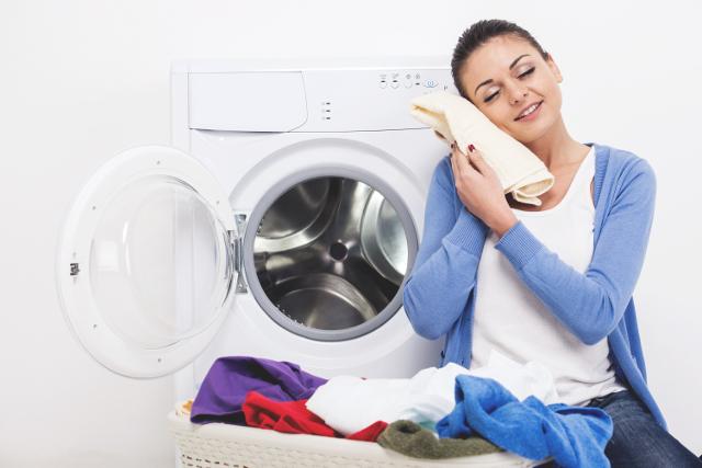 乾燥機で乾燥したタオルを顔につけている女性