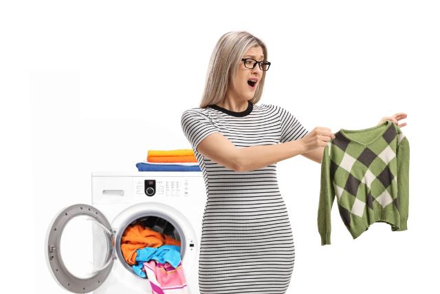 乾燥機でセーターが縮んでしまって驚く女性