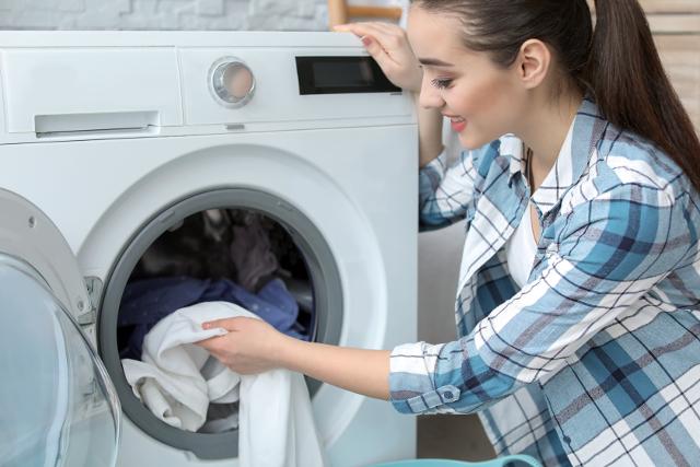 乾燥機から衣類を出す女性