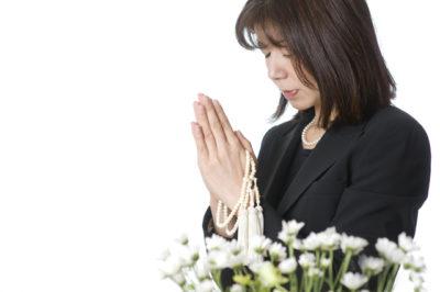 喪服で手を合わせる女性