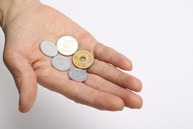 手のひらに小銭をのせている女性の手 1円・5円