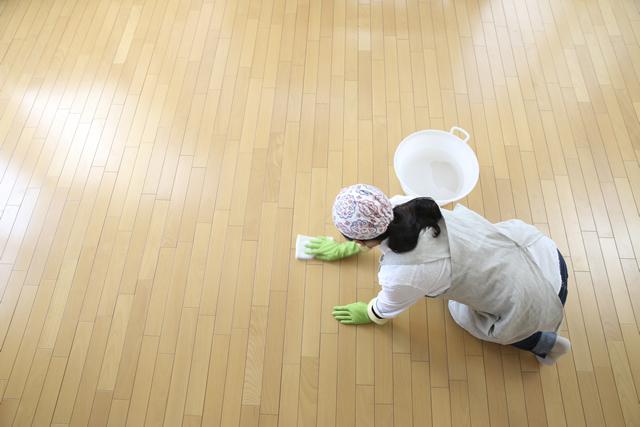 フローリングの拭き掃除をしている女性