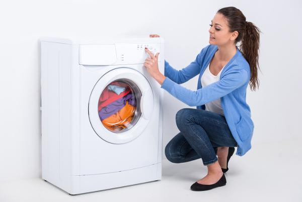 乾燥機のスイッチを入れる女性