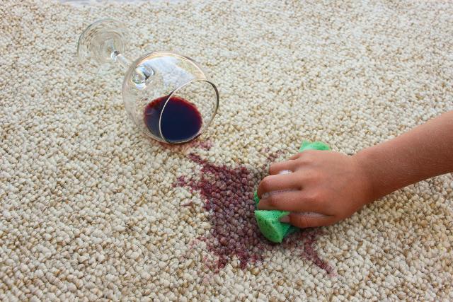 カーペットにこぼれたワインを拭く手