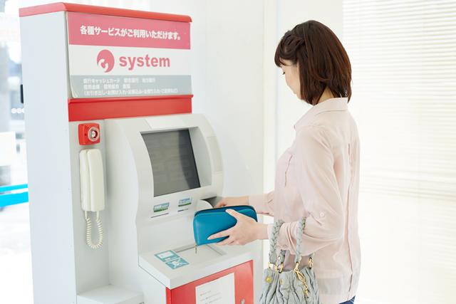 ATMからお金を引き出す女性
