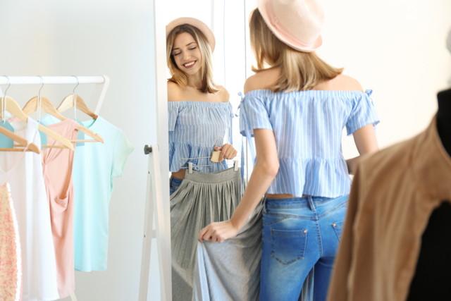 衣類と鏡を見るピンクの帽子の女性