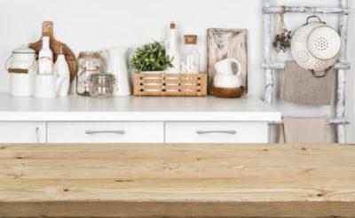 木のテーブルと、その後ろにキッチン用の小物が並んでいる
