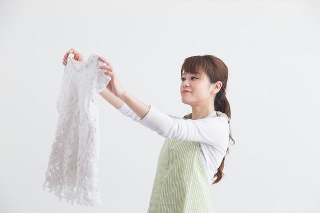 白い服を手にしている女性