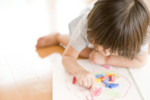 床で白い紙にお絵描きしているこども