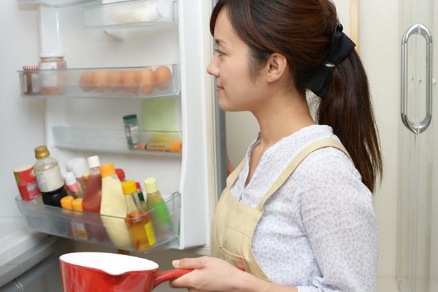 冷蔵庫を見る女性
