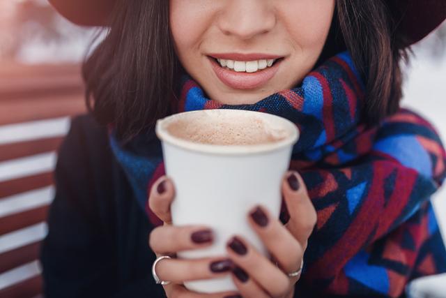 ホットコーヒーを持つ女性
