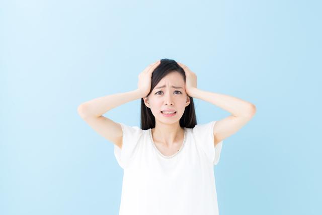 頭を抑える 女性