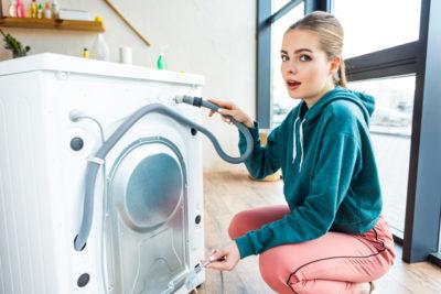 洗濯機をいじる女性