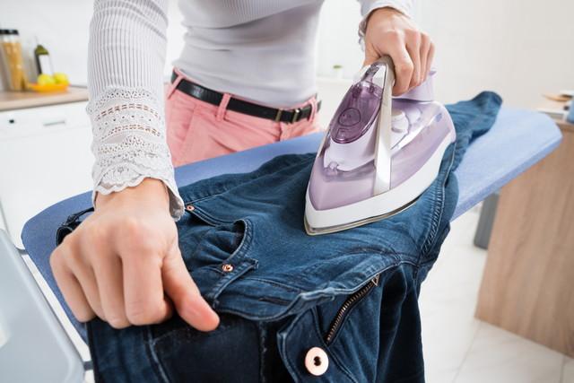 ズボンにアイロンをかけている女性