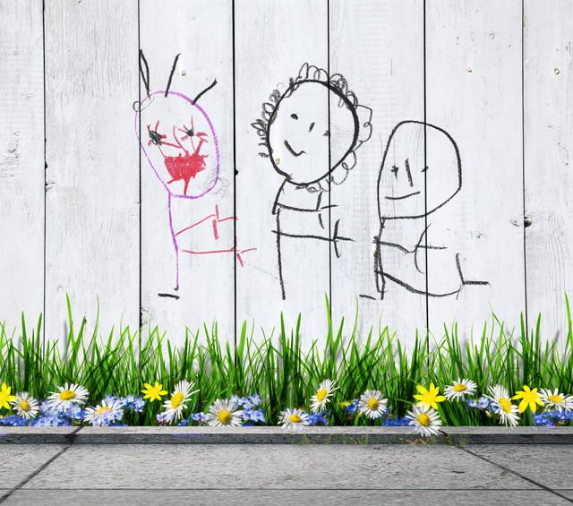 壁の落書きと花