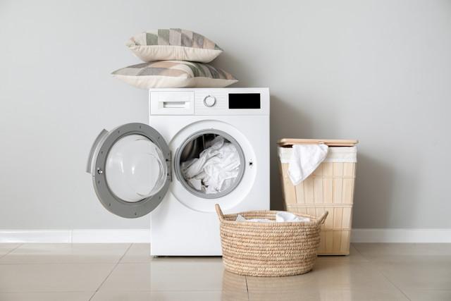 白い壁の近くに洗濯物を備えたモダンな洗濯機